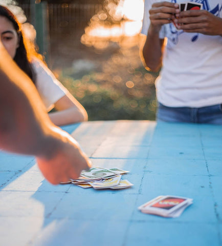 Family playing UNO at sunset on their summer vacation