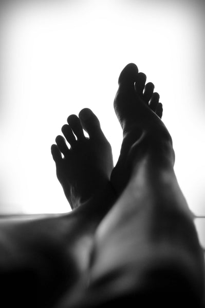 A pair of feet flexed in front of a white backdrop