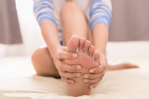 A woman massaging her injured foot on her bed at home