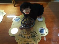 Needle Felted Niffler at the national space centre turning a big dial