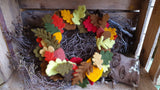 Autumnal wreath made from Needles felted leaves on a log with rustic wooden background