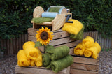 Needle felted sunflower with wool batts and carding machine on wooden crates