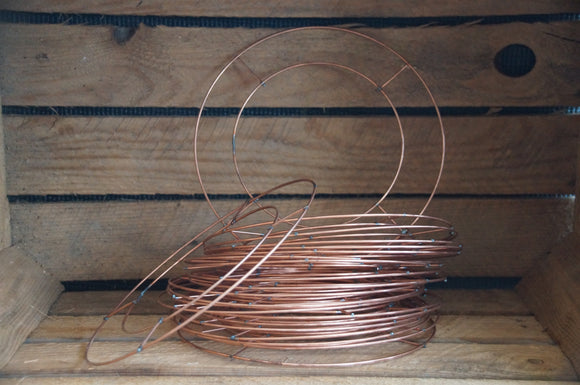pile of 8 inch wire wreath rings in a wooden background