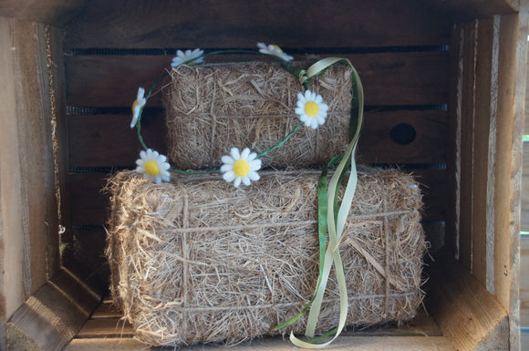 daisy circlet with cascading ribbons on small straw bales