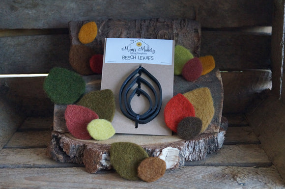 Needle felted leave in autumnal colours surrounding the beech leaf template set with rustic wooden background