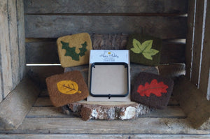 set of 4 woodland leaf themed coasters surrounding the coaster template in a rustic wooden background