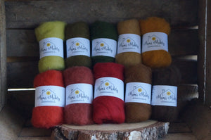10 autumnal shades of felting wool on a rustic wooden background