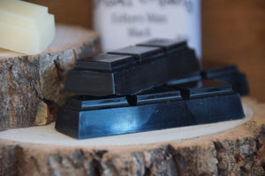 Needle Felters Wax in Natural, Pink and Black 3 square bars displayed on little log slices with a rustic wooden background