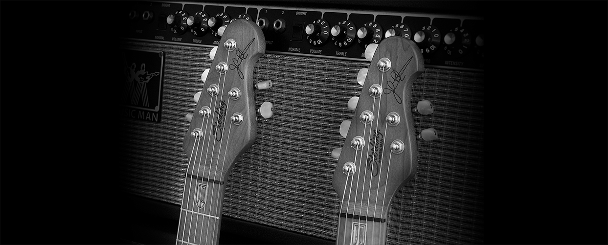 Two Sterling By Music Man guitars resting on an amp.