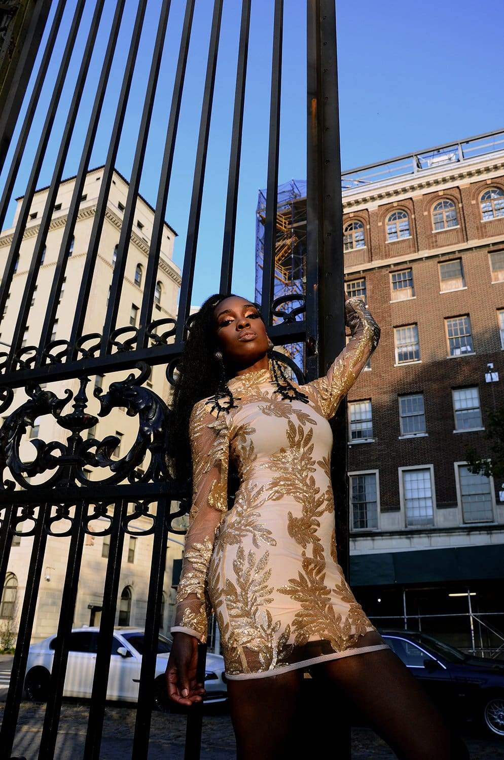 a person sitting on a bench in front of a fence
