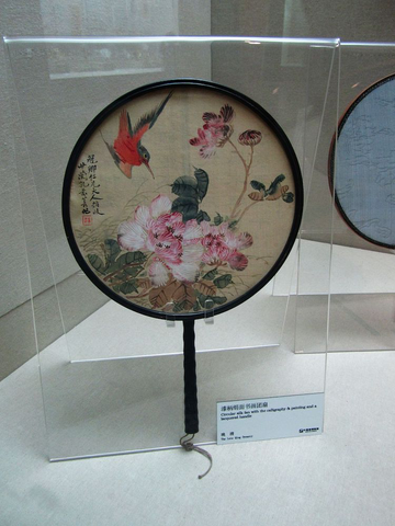 A circular silk fan with calligraphy, painting, and a lacquered handle, a courtesy of WikiMedia Commons.