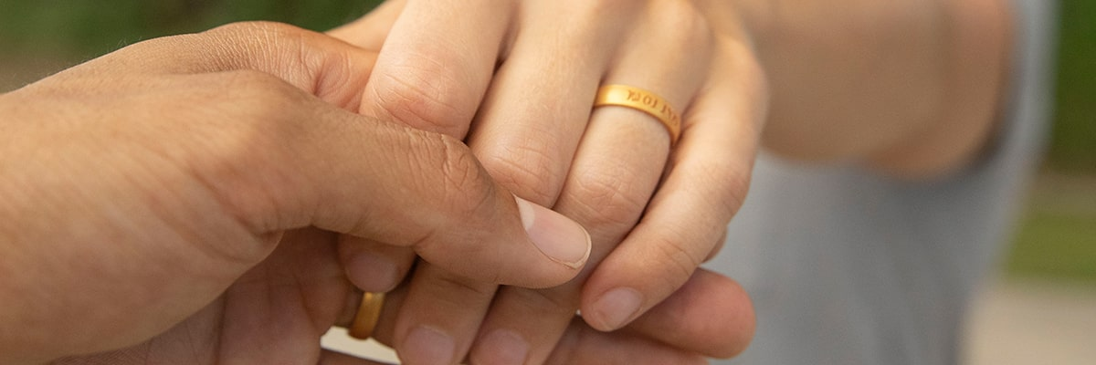 Close up photo of Garrett and Jessica holding hands while wearing their custom engraved gold color Enso Elements Ring.