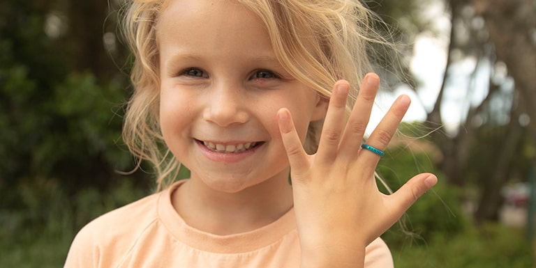 Close up of a cute little girl smiling while wearing her custom engraved Enso ring.