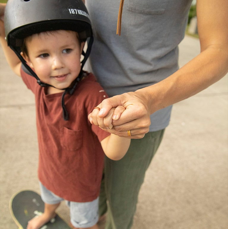 Close up of Garrett and son skateboarding together while wearing their custom engraved Enso Rings