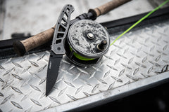 An open folding knife with a black stainless steel blade leaning against a fishing lure with a neon green fishing line.