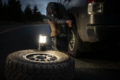 A man repairing a broken tire on his car using an LED lantern.