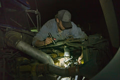 A mechanic using a stainless steel LED flashlight to inspect a broken and repair a broken car engine.