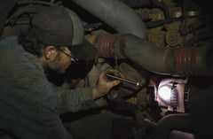 A mechanic inspecting a broken engine with an LED stainless steel penlight.