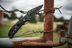 Stainless Steel Folding Knife Resting against Wire Fence, lifestyle photo.