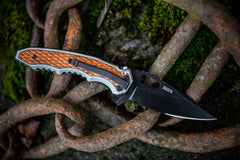 Stainless Steel Folding Knife resting open on rusted link chain, lifestyle photo