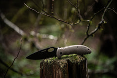 Stainless Steel Folding Knife Resting Open on Wooden Stump, lifestyle photo