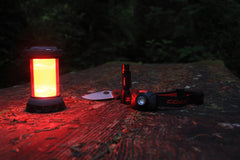An illuminated red light LED lantern on a wooden park bench next to a folding knife, flashlight, and headlamp.
