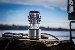 A COAST stainless steel lantern sitting on a wooden dock next to a rope on a sunny day with the ocean in the background.