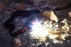 An LED headlamp sitting on gravel surrounded by rocks turned on to white light mode.