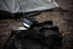 An illuminated COAST FL13 LED Headlamp sitting on a rock next to a gray tent.