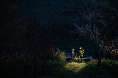 A man and a woman unloading a boat off of the river at night using LED headlamps.