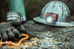 Headlamp Mounted On Hard Hat Sitting On Wet Rock Next to Thermos and Gloves, lifestyle photo