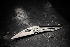 Stainless Steel Blade Folding Knife Laying Open on Dark Wet Surface, lifestyle photo