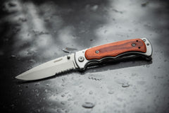 Stainless Steel Blade Folding Knife Laying on Dark Wet Surface, lifestyle photo