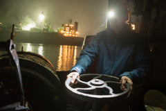 A man on a tugboat using an LED headlamp to turn a circular lever at night on a river.