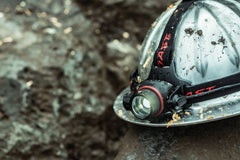LED Headlamp Mounted on Wet and Dirty Hard Hat Sitting on a Wet Rock, lifestyle photo