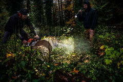 A man in the woods using a chainsaw to cut a log in half while his friend lights up the log with a large LED flashlight.