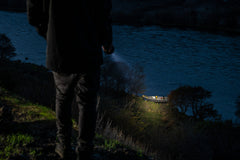 Man Shining LED Flashlight at Empty Boat on River Bank, lifestyle photo