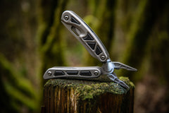 Spring Loaded Pliers Resting Open On Tree Stump with LED Light Turned On, lifestyle photo