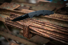 Black Stainless Steel Knife Resting Open on Rusty Steel Bars, lifestyle photo