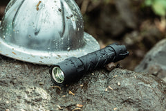 LED Flashlight Turned On Resting Next to Wet Hard Hat on Wet Rock, lifestyle photo