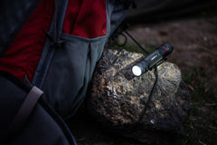 LED Flashlight Resting on Rock Illuminating Campfire, lifestyle photo