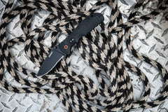 Stainless Steel Blade Folding Knife Laying Open on Black and White Rope, lifestyle photo
