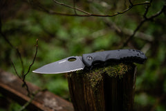 Stainless Steel Knife with Nylon Handle Resting Open on Tree Stump, lifestyle photo