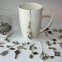 tea infuser with range of removable charms in white mug