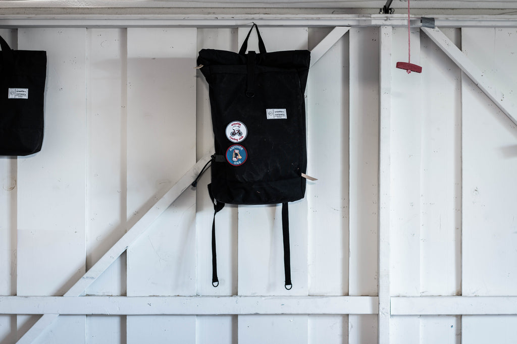 commuter-rolltop-backpack-hanging-on-wall