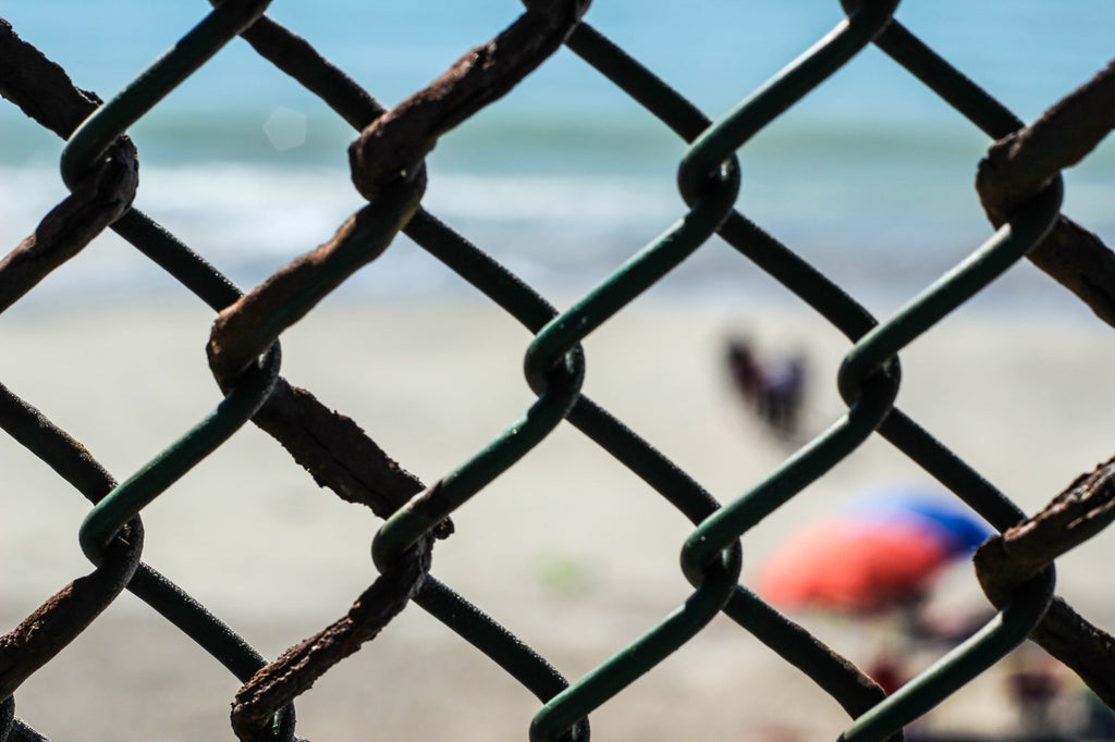 looking-through-fence-hole-to-beach