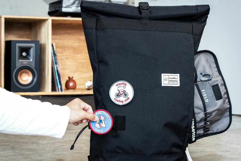 commuter-rolltop-backpack-space-black-putting-patch-on