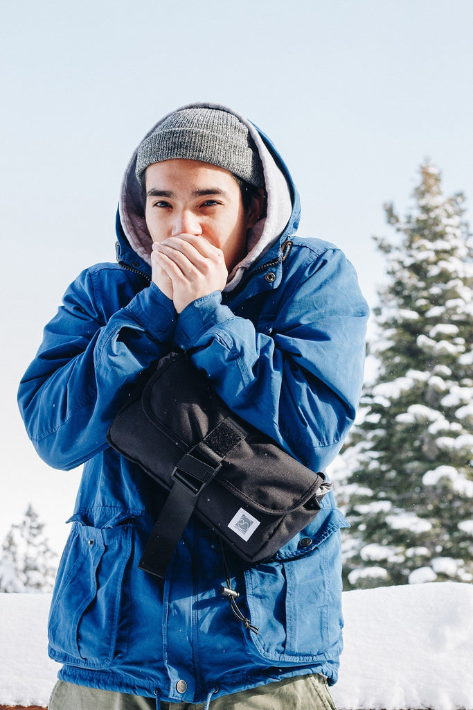 man-warming-up-hands-outdoor-snow-sling-bag