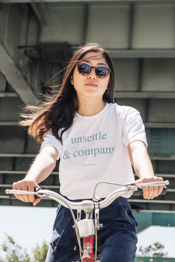 model-wearing-unsettle-city-tee-on-vintage-bike