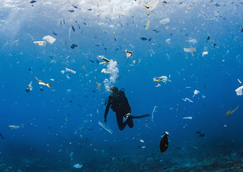 Diver diving in middle of plastic waste